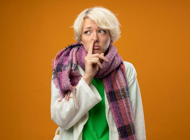 Femme malsaine malade aux cheveux courts en écharpe chaude touchant son nez avec le doigt malheureux et triste debout sur le mur orange