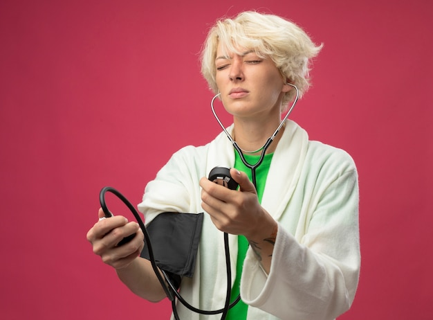 Femme malsaine malade aux cheveux courts avec stéthoscope mesurant sa pression artérielle se sentant mal debout sur fond rose