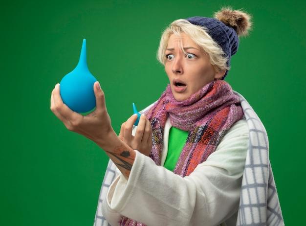 Femme malsaine malade avec des cheveux courts dans une écharpe chaude et un chapeau enveloppé dans une couverture tenant un lavement en le regardant être surpris debout sur fond vert