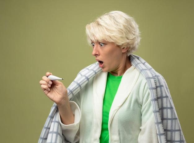 Femme malsaine malade avec les cheveux courts enveloppés dans une couverture se sentant mal à la recherche de thermomètre choqué debout sur un mur léger