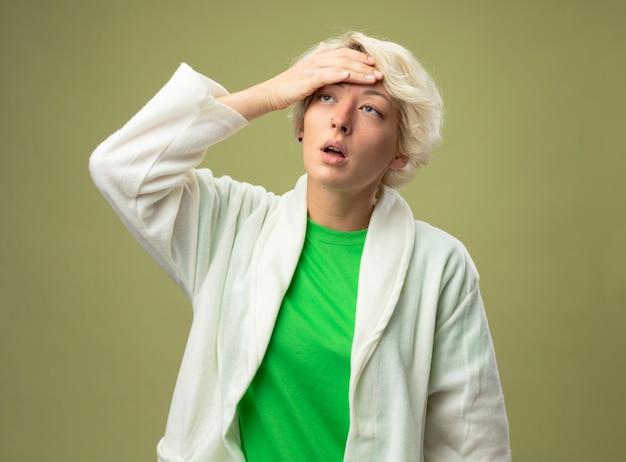 Femme malsaine malade avec les cheveux courts se sentir mal en touchant son front ayant la température debout sur un mur léger
