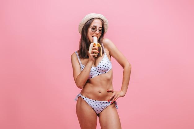 La femme mange une banane dans un chapeau de maillot de bain et des lunettes de soleil sur un mur rose