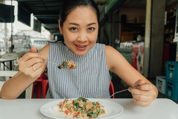 Une femme mange du porc et du basilic sautés au riz thaïlandais.