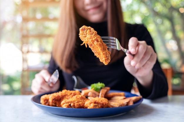 Une femme mange du poulet frit et des frites dans un restaurant