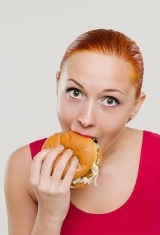 Femme mange un hamburger