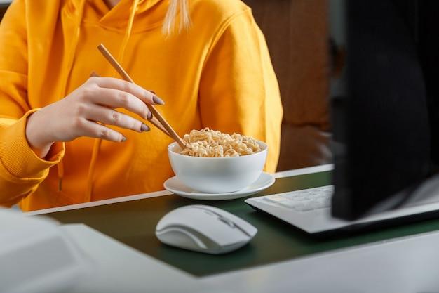 Une femme mange des nouilles avec des baguettes derrière un ordinateur sur son lieu de travail à domicile, au bureau à domicile pendant un jeu vidéo ou en regardant un film ou un processus éducatif. collation rapide de malbouffe pendant les heures supplémentaires. nouilles délicieuses.