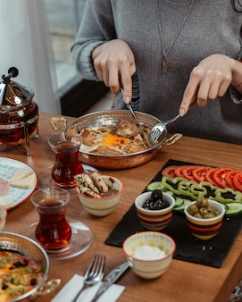 Une femme mange une omelette avec du thé noir et des aliments tout autour.
