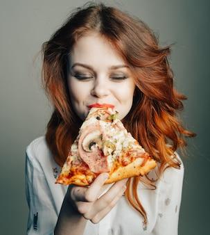 Femme mange de la pizza avec plaisir