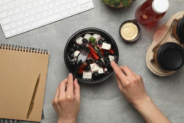 Femme mange de la salade dans une boîte à emporter sur le mur gris. livraison de nourriture