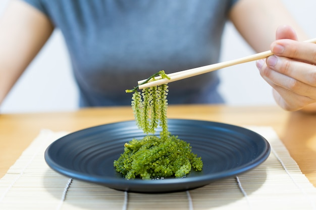 Femme mangeant une algue de raisin.