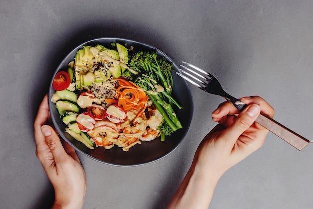 Femme mangeant un bol de bouddha avec des crevettes au quinoa et une vinaigrette au tahini