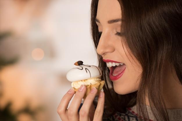 Femme mangeant des bonbons près de sapin de noël