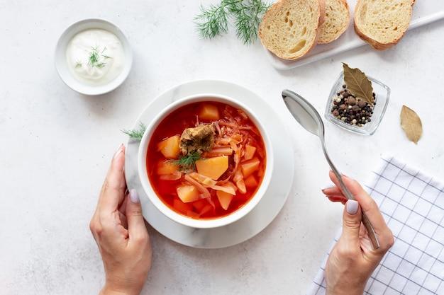 Femme mangeant du bortsch rouge avec des légumes