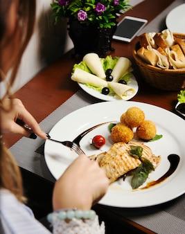 Femme mangeant un filet de saumon cuit au four avec pommes de terre et rouleaux de fromage et mélange de légumes.