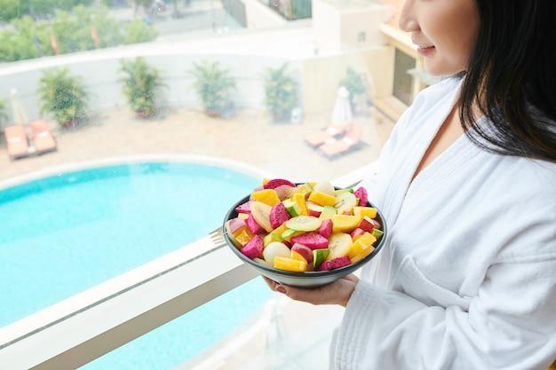 Femme mangeant des fruits à l'hôtel