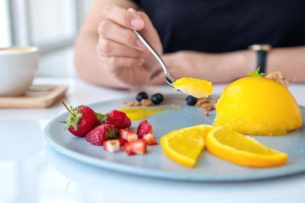 Une femme mangeant un gâteau à l'orange avec un mélange de fruits à la cuillère au café