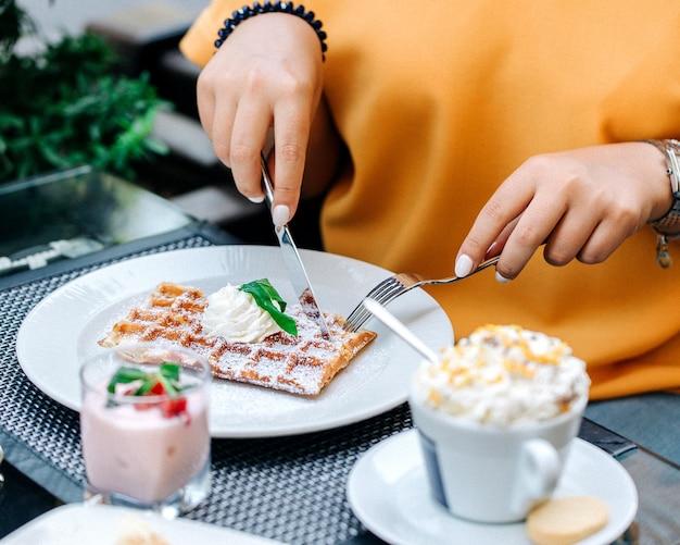 Femme mangeant des gaufres garnies de crème