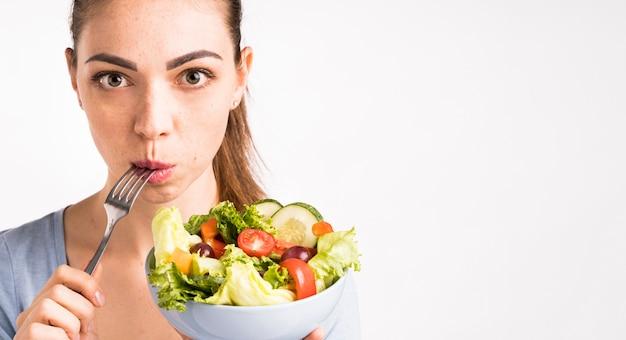 Femme mangeant un gros plan de salade