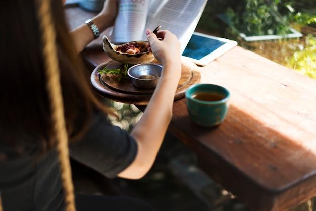 Femme mangeant en lisant un livre