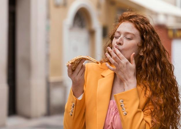 Femme mangeant de la nourriture de rue à l'extérieur