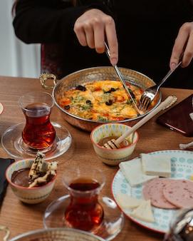 Une femme mangeant une omelette dans une casserole, autour d'une table, avec du miel, du fromage, du salami et du thé noir.