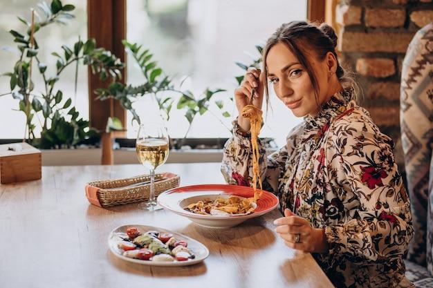 Femme mangeant des pâtes dans un restaurant italien