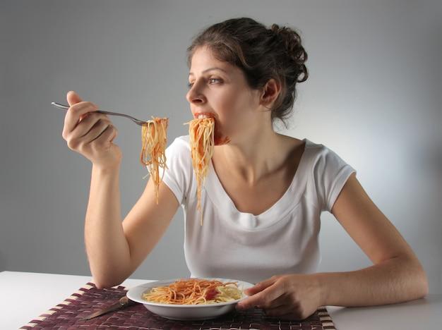 Femme mangeant des pâtes