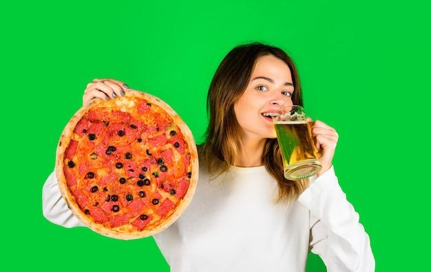 Femme mangeant de la pizza femme souriante tient un verre avec de la bière nourriture déjeuner fille heureuse tenant une pizza et de la bière
