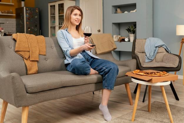 Femme mangeant de la pizza en regardant la télévision