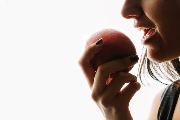 Femme mangeant une pomme rouge