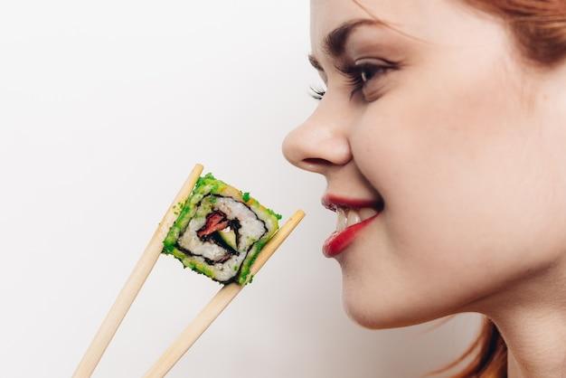 Femme mangeant des rouleaux avec des baguettes en bambou