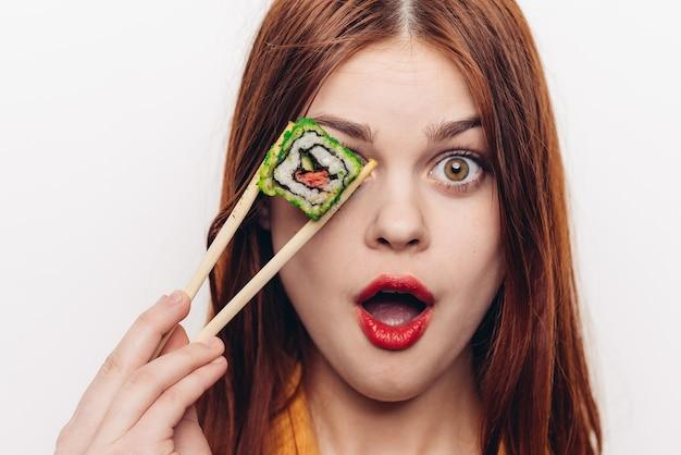 Femme mangeant des rouleaux de couleur avec des baguettes en bambou, cuisine asiatique