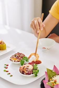 Femme mangeant une salade de crevettes