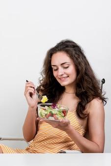 Femme mangeant une salade de laitue