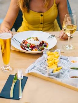 Femme mangeant une salade saine avec du fromage burrata, de la roquette et de la salade de betteraves