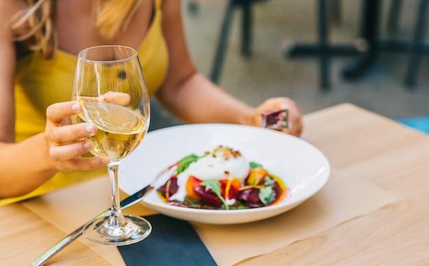 Femme mangeant une salade saine avec du fromage burrata, salade de roquette et tomates et tenant du vin blanc dans un verre