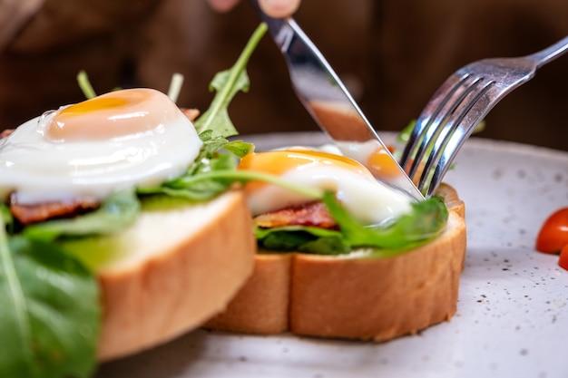 Une femme mangeant un sandwich au petit déjeuner avec des œufs, du bacon et de la crème sure au couteau et cuillère dans une assiette sur une table en bois