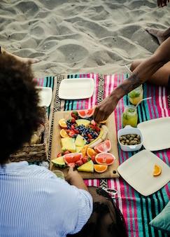 Femme mangeant un sandwich à la plage