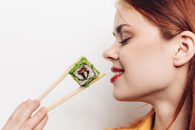 Femme, manger, coloré, rouleaux, bambou, baguettes, nourriture asiatique, lumière, espace