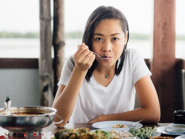 Femme manger un ensemble de fruits de mer thaïlandais épicés.