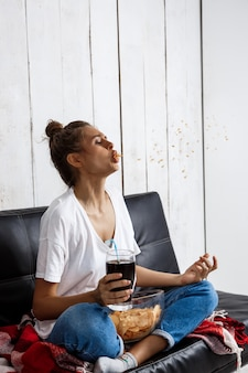 Femme manger des frites, boire du soda, regarder la télévision, assis sur le canapé.