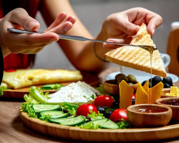 Femme, manger, miel, toast, petit déjeuner
