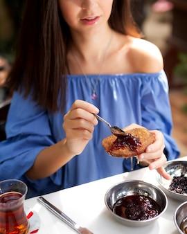 Femme, manger, pain grillé français, à, confiture fraise