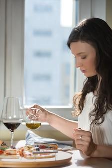 Femme, manger des pizzas maison et boire du vin rouge