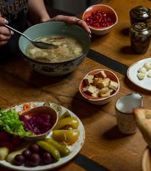 Femme, manger, soupe poulet, à, herbes, et, épices, autour