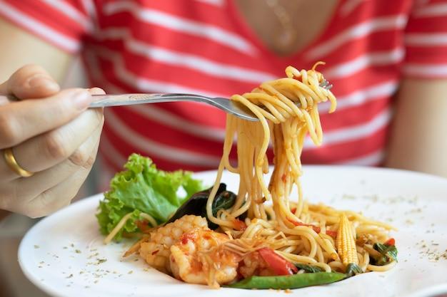 Femme, manger, spaghetti, fruits mer