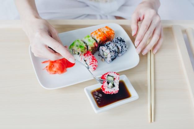 Femme, manger, sushi, fourchette