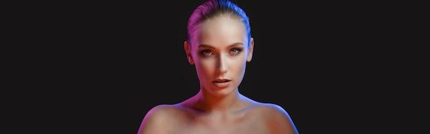 Femme mannequin de haute couture dans des néons lumineux colorés qui posent en studio, boîte de nuit. portrait de la belle fille séduisante sexy en uv. sur fond vif coloré.
