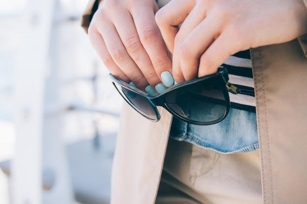 Femme, manteau beige, lunettes soleil, mains
