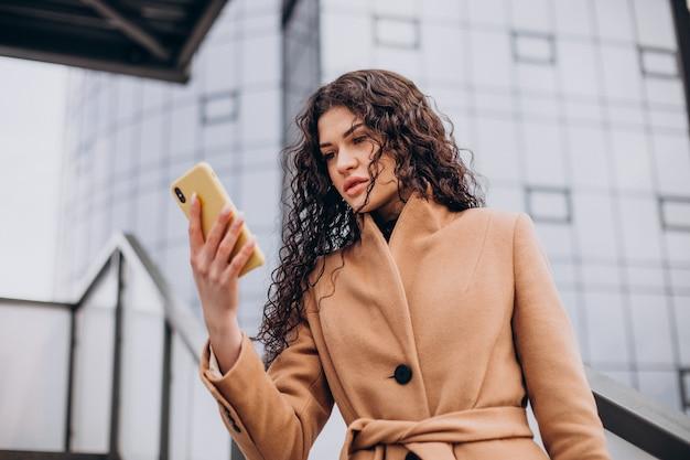 Femme en manteau beige marchant dans la ville